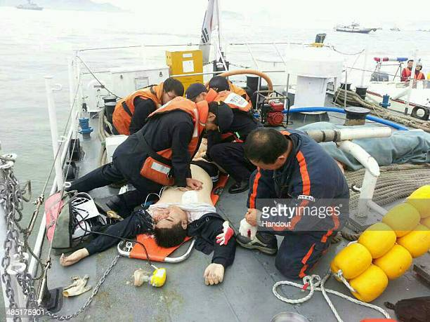 In this handout image provided by the West Regional Headquarters Korea Coast Guard an injured passenger who was on a sinking ship is rescued by South...
