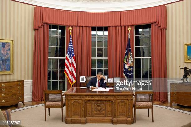 In this handout image provided by The White House President Barack Obama edits his remarks in the Oval Office prior to making a televised statement...