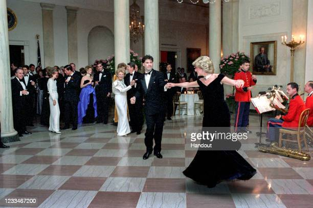 In this handout image provided by The White House, Princess Diana dances with John Travolta in Cross Hall at the White House during an official...