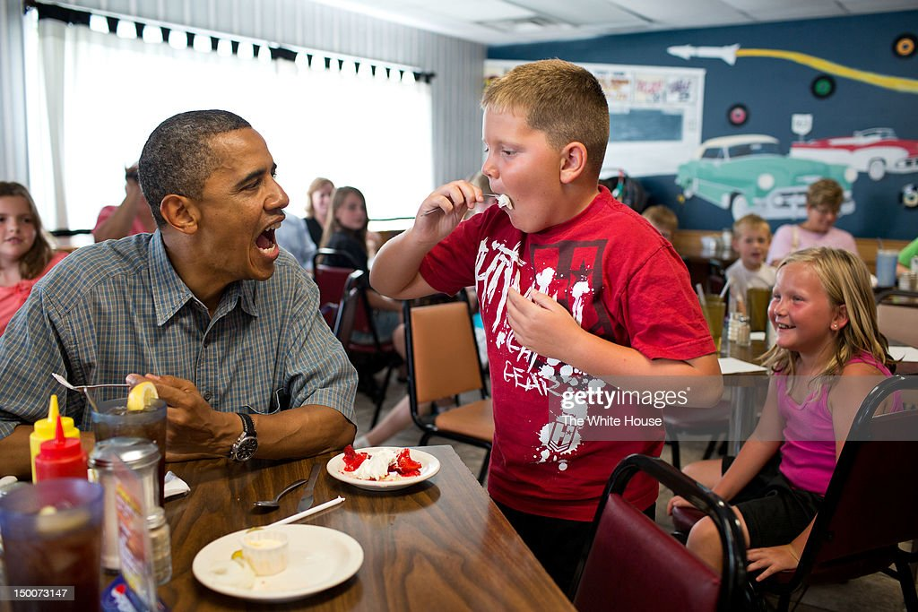 In this handout image provided by the White House, U.S. President Barack Obama shares his strawberry pie with a boy during a lunch stop at Kozy Corners restaurant in Oak Harbor, Ohio, July 5, 2012.