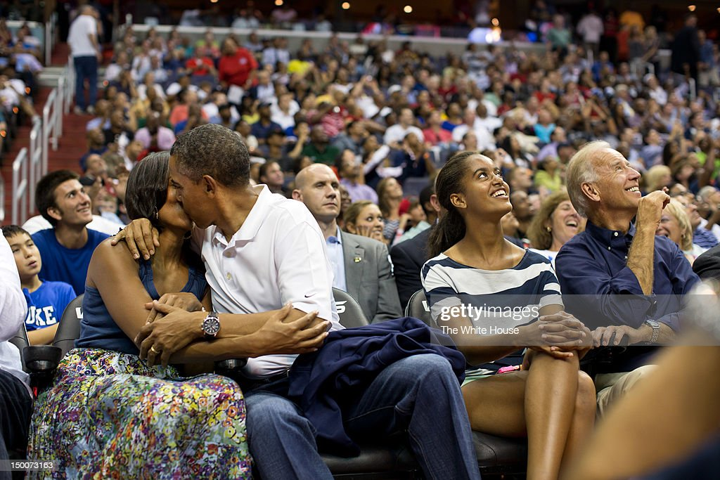 In this handout image provided by the White House, U.S. President Barack Obama kisses First Lady Michelle Obama for the 'Kiss Cam' while Vice President Joe Biden and Malia Obama look up at the jumbotron, during the U.S. Men's Olympic basketball team's game against Brazil at the Verizon Center on July 16, 2012 in Washington, D.C.