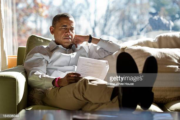 In this handout image provided by The White House, U.S. President Barack Obama reads briefing material while meeting with advisors inside his cabin...