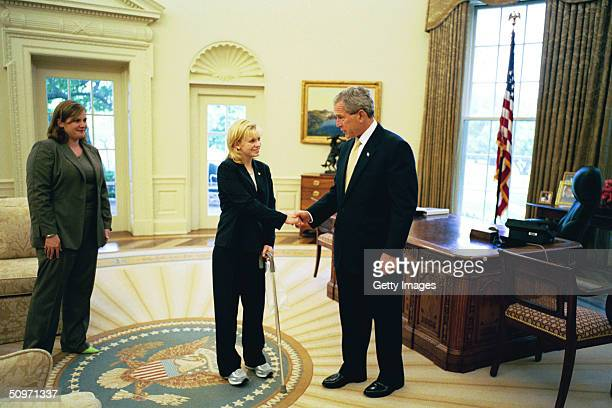 In this handout image provided by the White House US President George W Bush meets with Private Jessica Lynch as her friend Alyssa Gregg watches in...