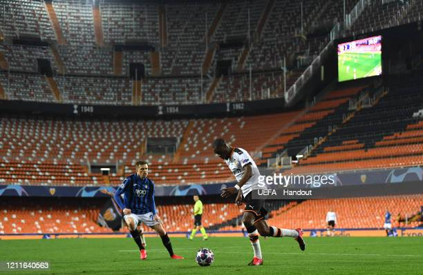 In this handout image provided by UEFA, A general view as Josip Ilicic of Atalanta closes down Geoffrey Kondogbia of Valencia during the UEFA...