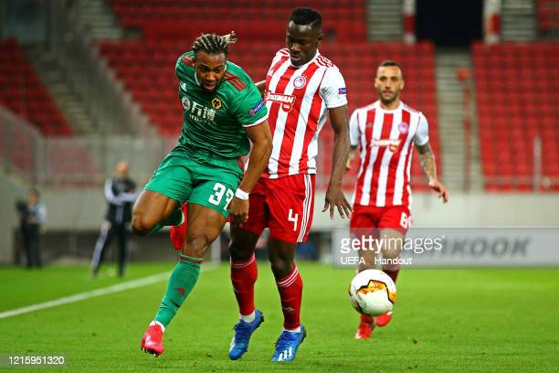 In this handout image provided by UEFA Adama Traore of Wolverhampton Wanderers is challenged by Mady Camara of Olympiacos FC during the UEFA Europa...