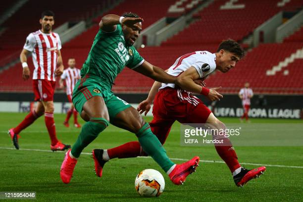 In this handout image provided by UEFA Adama Traore of Wolverhampton Wanderers is challenged by Konstantinos Tsimikas of Olympiacos FC during the...