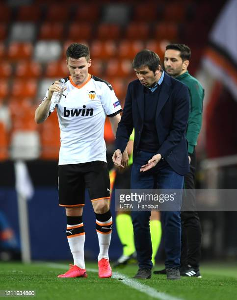 In this handout image provided by UEFA Albert Celades head coach of Valencia speaks with Kevin Gameiro of Valencia during the UEFA Champions League...