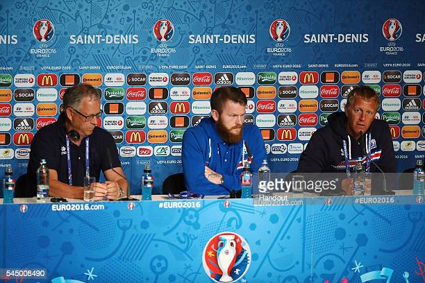 In this handout image provided by UEFA Aron Gunnarsson and coaches Lars Lagerback and Heimir Hallgrimsson of Iceland attend a press conference at...
