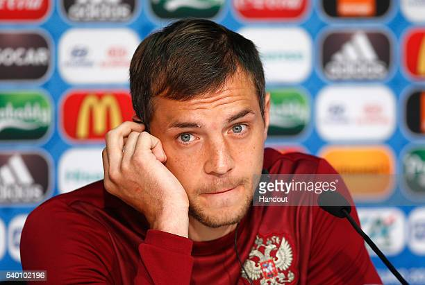 In this handout image provided by UEFA, Artem Dzyuba of Russia listens to the media's questions during the Russia Press Conference at the Stade...