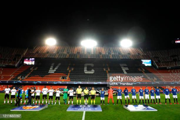 In this handout image provided by UEFA Both teams line up in an empty stadium ahead of the UEFA Champions League round of 16 second leg match between...