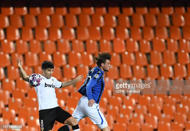 In this handout image provided by UEFA Carlos Soler of Valencia battles for possession with Hans Hateboer of Atalanta during the UEFA Champions...