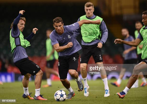 In this handout image provided by UEFA Cristiano Ronaldo of Real Madrid goes past Luka Modric during a training session prior to the UEFA Champions...