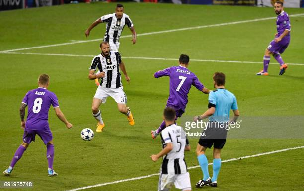 In this handout image provided by UEFA Cristiano Ronaldo of Real Madrid scores his sides first goal during the UEFA Champions League Final between...