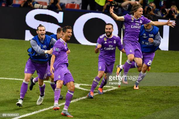 In this handout image provided by UEFA Cristiano Ronaldo of Real Madrid celebrates scoring his sides third goal with his Real Madrid team mates...