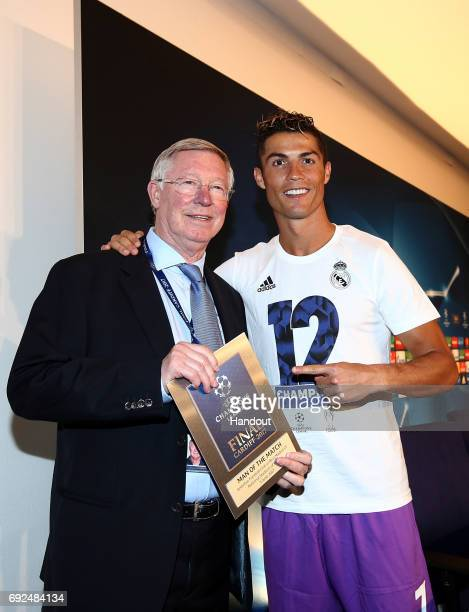In this handout image provided by UEFA Cristiano Ronaldo of Real Madrid poses with the Man of the Match award and Sir Alex Ferguson after the UEFA...