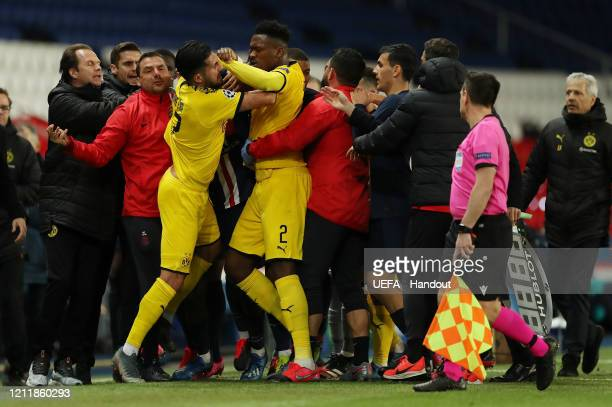 In this handout image provided by UEFA, Emre Can and Dan-Axel Zagadou of Borussia Dortmund clash with the PSG bench during the UEFA Champions League...