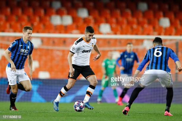 In this handout image provided by UEFA Ferran Torres of Valencia runs with the ball as Jose Luis Palomino of Atalanta looks on during the UEFA...