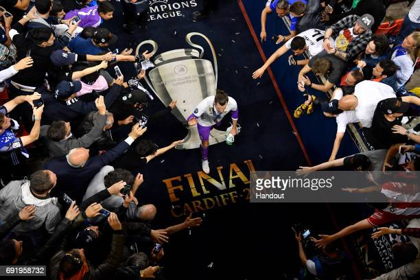 In this handout image provided by UEFA Gareth Bale of Real Madrid walks back to the dressing room after the UEFA Champions League Final between...