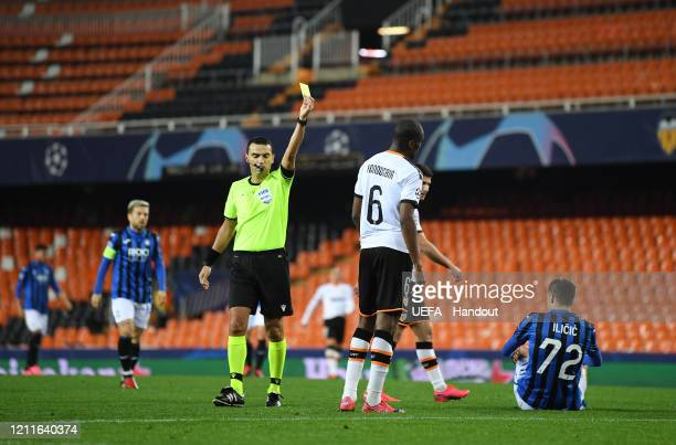 In this handout image provided by UEFA, Geoffrey Kondogbia of Valencia is shown a yellow card by referee Ovidiu Hategan during the UEFA Champions...
