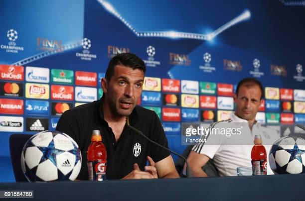 In this handout image provided by UEFA Gianluigi Buffon of Juventus talks during a press conference as Massimiliano Allegri Manager of Juventus looks...