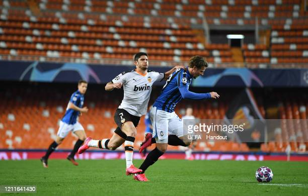 In this handout image provided by UEFA Goncalo Guedes of Valencia tackles Hans Hateboer of Atalanta during the UEFA Champions League round of 16...