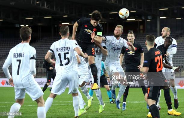 In this handout image provided by UEFA, Harry Maguire of Manchester United wins a header during the UEFA Europa League round of 16 first leg match...