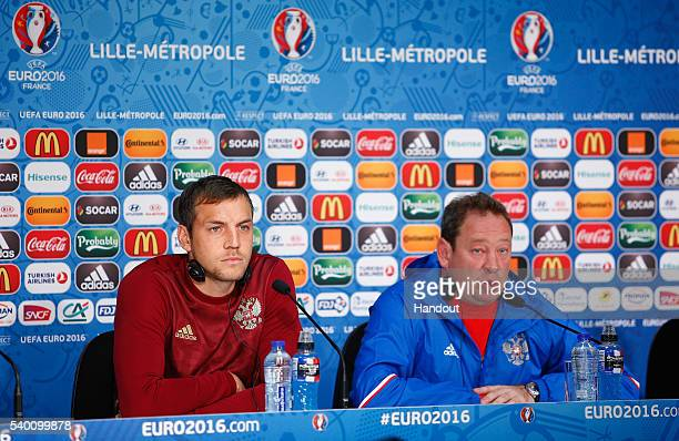 In this handout image provided by UEFA Head Coach Leonid Slutski of Russia talks to the media with Artem Dzyuba during the Russia Press Conference at...