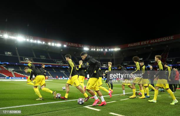In this handout image provided by UEFA, Jadon Sancho of Borussia Dortmund and his team mates warm up prior to the UEFA Champions League round of 16...