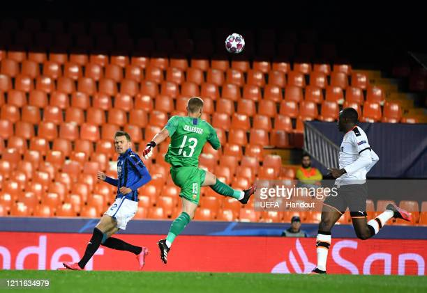 In this handout image provided by UEFA Jasper Cillessen of Valencia clears the ball from a challenge by Josip Ilicic of Atalanta during the UEFA...