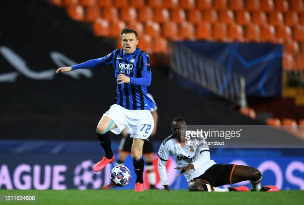 In this handout image provided by UEFA Josip Ilicic of Atalanta controls the ball as Mouctar Diakhaby of Valencia looks on during the UEFA Champions...