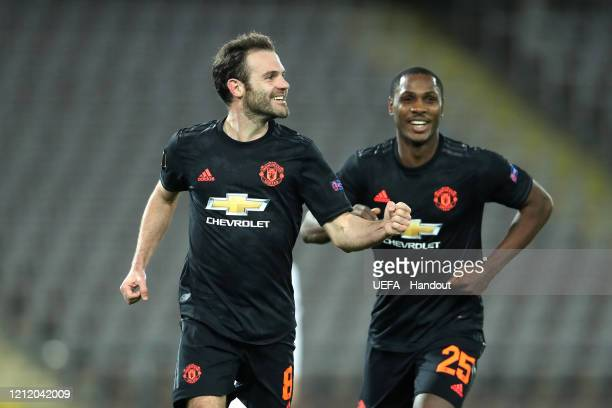 In this handout image provided by UEFA Juan Mata of Manchester United celebrates with Odion Ighalo after scoring his team's third goal during the...