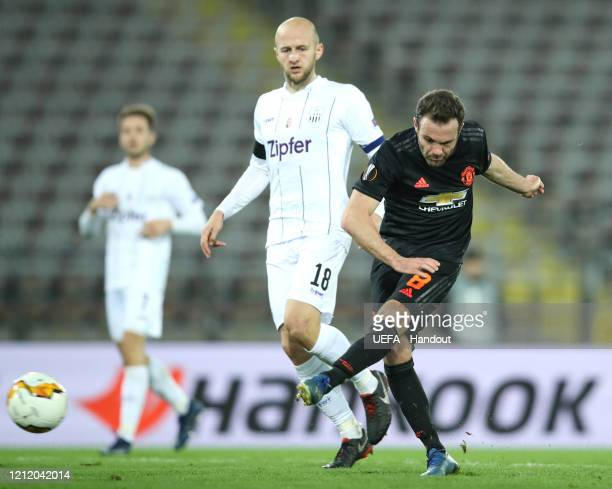 In this handout image provided by UEFA Juan Mata of Manchester United scores his team's third goal during the UEFA Europa League round of 16 first...