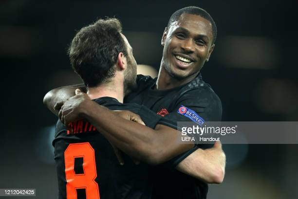 In this handout image provided by UEFA, Juan Mata of Manchester United celebrates with Odion Ighalo after scoring his team's third goal during the...