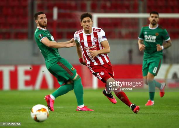 In this handout image provided by UEFA, Konstantinos Tsimikas of Olympiacos FC gets away from Matt Doherty of Wolverhampton Wanderers during the UEFA...