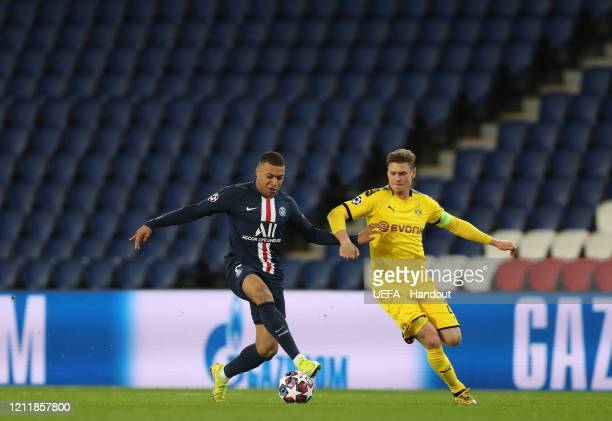 In this handout image provided by UEFA Kylian Mbappe of Paris SaintGermain is challenged by Lukasz Piszczek of Borussia Dortmund during the UEFA...