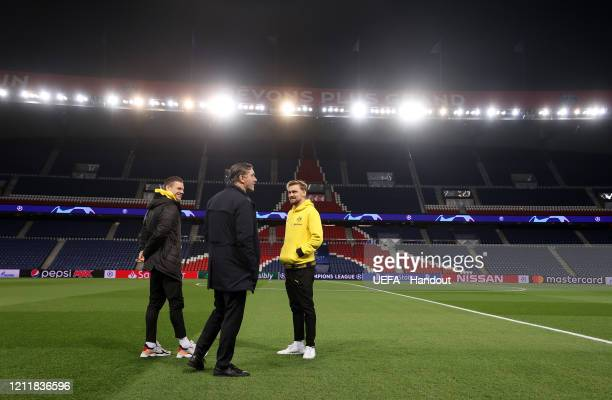 In this handout image provided by UEFA Lukasz Piszczek and Marcel Schmelzer of Borussia Dortmund and Michael Zorc Team Manager of Borussia Dortmund...