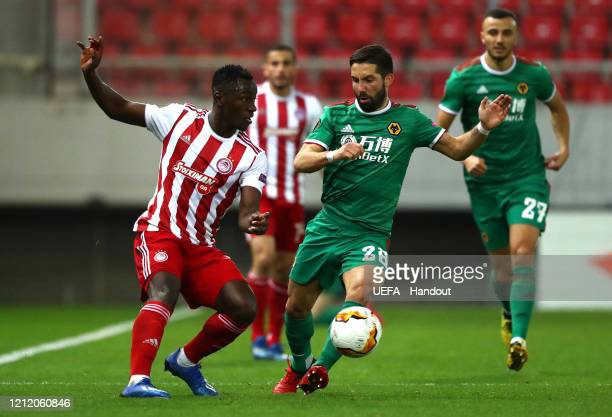 In this handout image provided by UEFA Mady Camara of Olympiacos FC is challenged by Joao Moutinho of Wolverhampton Wanderers during the UEFA Europa...