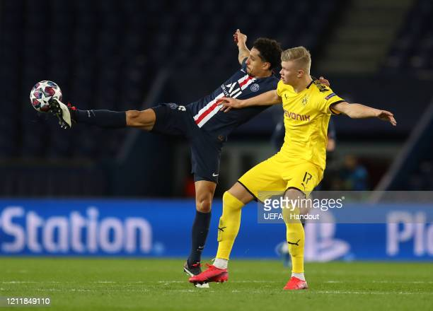 In this handout image provided by UEFA, Marquinhos of Paris Saint-Germain is challenged by Erling Haaland of Borussia Dortmund during the UEFA...