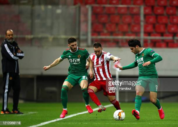 In this handout image provided by UEFA Mathieu Valbuena of Olympiacos FC is challenged by Joao Moutinho and Pedro Neto of Wolverhampton Wanderers as...