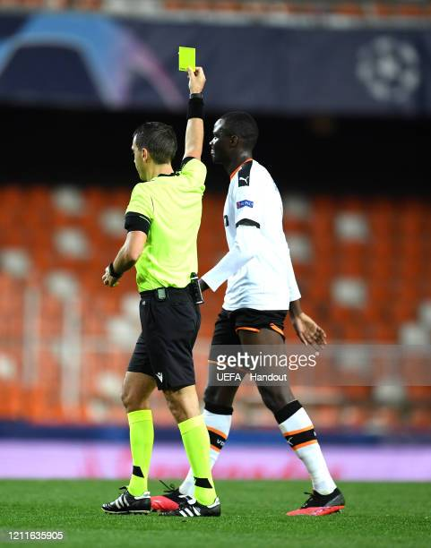 In this handout image provided by UEFA Mouctar Diakhaby of Valencia received the yellow card during the UEFA Champions League round of 16 second leg...