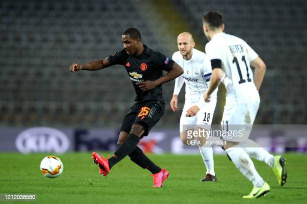 In this handout image provided by UEFA Odion Ighalo of Manchester United is challenged by Gernot Trauner and Dominik Reiter of LASK during the UEFA...