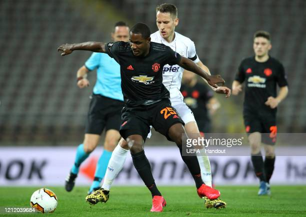 In this handout image provided by UEFA Odion Ighalo of Manchester United is challenged by Christian Ramsebner of LASK during the UEFA Europa League...