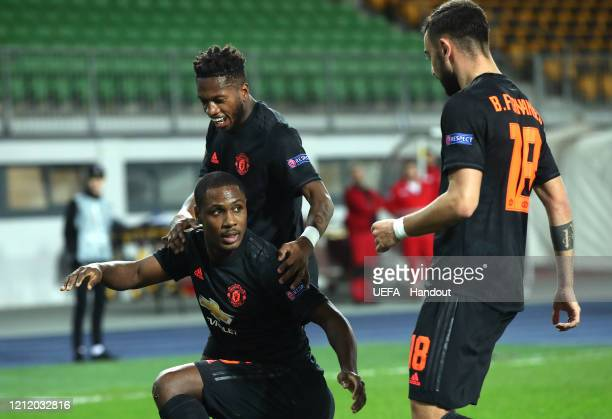 In this handout image provided by UEFA Odion Ighalo of Manchester United celebrates with Fred and Bruno Fernandes after scoring his team's first goal...