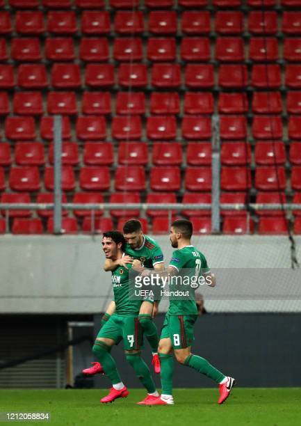 In this handout image provided by UEFA Pedro Neto of Wolverhampton Wanderers celebrates with Ruben Vinagre and Ruben Neves after scoring his team's...
