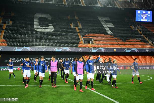 In this handout image provided by UEFA Players walk on the pitch after the UEFA Champions League round of 16 second leg match between Valencia CF and...
