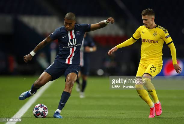 In this handout image provided by UEFA Presnel Kimpembe of Paris SaintGermain is challenged by Thorgan Hazard of Borussia Dortmund during the UEFA...