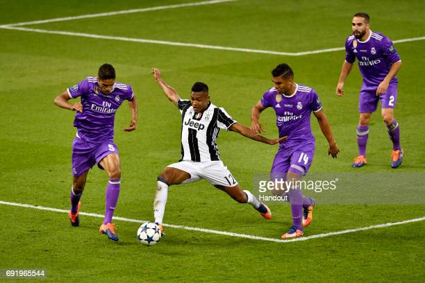 In this handout image provided by UEFA Raphael Varane of Real Madrid and Casemiro of Real Madrid attempt to tackle Alex Sandro of Juventus during the...