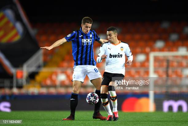 In this handout image provided by UEFA Robin Gosens of Atalanta battles for possession with Rodrigo Moreno of Valencia during the UEFA Champions...