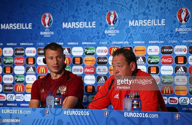 In this handout image provided by UEFA, Russia head coach Leonid Sloutski and Vasili Berezutski face the media during the Russia Press Conference on...