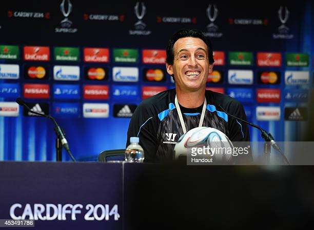 In this handout image provided by UEFA Sevilla FC coach Unai Emery smiles during the Sevilla FC press conference at Cardiff City Stadium on August 11...
